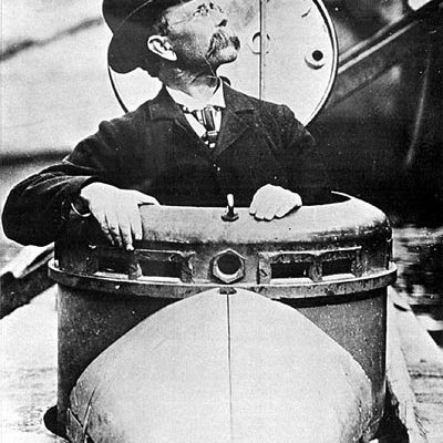 Photograph of John Holland, inventor of the submarine from Paterson and Newark, emerging from the Holland submarine, 1898